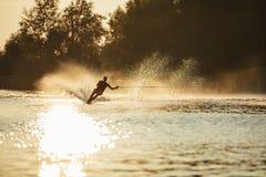 Man riding wakeboard on lake water. Man water skiing at sunset. Man riding wakeboard on lake water Stock Photography