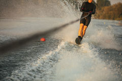 Man riding wakeboard on wave of motorboat Royalty Free Stock Image