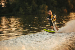 Man riding wakeboard on wave of motorboat. In a lake. Male water skiing behind a boat Stock Image