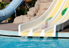 Man riding a water slide Stock Images