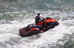 Riding Waves on a Red and Black Jetski. Man riding waves on a red and black jetski off Miami Beach on the Florida Intra-coastal Waterway royalty free stock photography