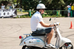 Man riding a white retro scooter Stock Photography