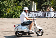 Man riding a white retro scooter Royalty Free Stock Photography