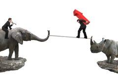 Man ridningelefanten mot noshörning en annan bärande arro för man Fotografering för Bildbyråer