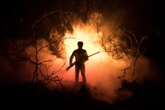 Man with riffle at spooky forest at night with light, or War Concept. Military silhouettes fighting scene on war fog sky backgroun. D, World War Soldier Royalty Free Stock Photos
