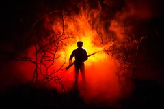 Man with riffle at spooky forest at night with light, or War Concept. Military silhouettes fighting scene on war fog sky backgroun. D, World War Soldier Stock Images