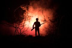 Man with riffle at spooky forest at night with light, or War Concept. Military silhouettes fighting scene on war fog sky backgroun. D, World War Soldier Royalty Free Stock Photography