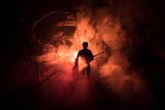 Man with riffle at spooky forest at night with light, or War Concept. Military silhouettes fighting scene on war fog sky backgroun. D, World War Soldier Royalty Free Stock Image