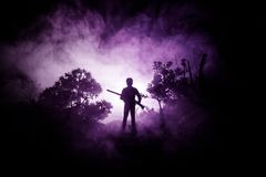 Man with riffle at spooky forest at night. Strange silhouette of hunter in a dark spooky forest at night, mystical landscape surre. Al lights with creepy man and Stock Image