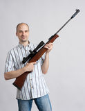 Man with rifle. On gray background Royalty Free Stock Photo