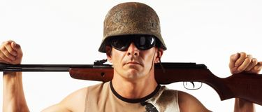 Man with rifle. Man in combat helmet and sunglasses holding a rifle over his shoulders, caucasian/white stock photo