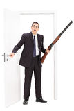 Man with rifle standing by a door. Full length portrait of a man with rifle standing by a door isolated on white background Royalty Free Stock Photo
