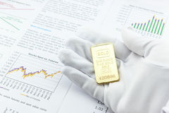 Man right hand with a white handy glove is showing / presenting an one ounce gold bar to a customer. Stock Photography