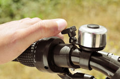 Man ringing a bicycle bell. Closeup of the hand of a man ringing a bicycle bell Royalty Free Stock Images