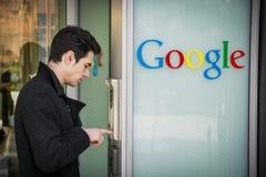 Man ringing the intercom at Google offices Stock Photo