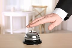 Man ringing service bell. In hotel lobby Royalty Free Stock Image