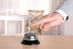Man ringing service bell. In hotel lobby Royalty Free Stock Photography