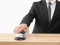 Man ringing in service bell. On reception desk Stock Photography