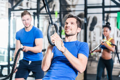 Man at rings doing fitness exercise in gym Royalty Free Stock Image