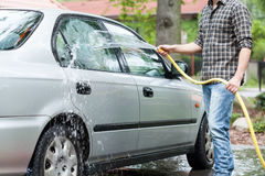 Man rinsing foam from car Royalty Free Stock Images