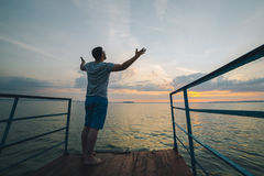 Man rises hands up on the lake pier Royalty Free Stock Photography