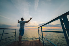 Man rises hands up on the lake pier Royalty Free Stock Image