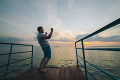 Man rises hands up on the lake pier Royalty Free Stock Images