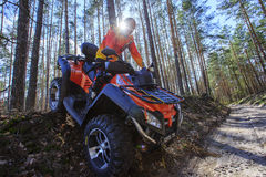 Man rises a quad bike in the forest. Royalty Free Stock Photos