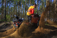 Man rises a quad bike in the forest. Stock Photography