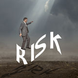 Man risking it. Business man walking on a gear with an urban silhouette behind. Concept for risk and ideas, all leading to success Stock Photography