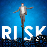 Man risking it. Casual business man walking on a gear with an urban silhouette behind. Concept for risk and ideas, all leading to success Stock Photo