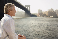 Man By River And Brooklyn Bridge Royalty Free Stock Photos