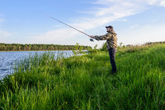 Man on the river throws a spinning fishing. Bearded man in a blue baseball cap on the river throws a spinning fishing Stock Images