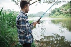 Man on the riverbank fishing fish. Portrait of man standing on the riverbank fishing fish Stock Image