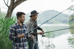 Man on the riverbank fishing fish. Portrait of two men on the riverbank fishing fish with friend Royalty Free Stock Photos