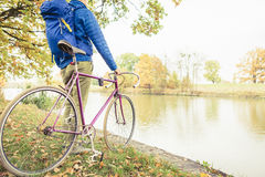 Man with road bike looking at river view in park. Male commuter and fixed gear bicycle relaxing in green park. Sport fitness motivation and inspiration in Stock Photo