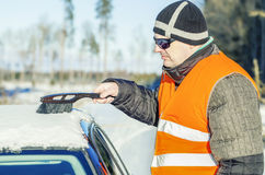 Man on the road cleans with brush the car out of the snow Stock Photo
