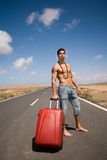 Man on the road with his suitcase. Under the blue sky Stock Photo