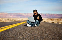 Man on road with laptop Royalty Free Stock Image