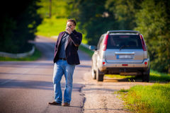 Man on a road near his car Stock Images