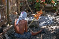 A man roast a whole pig on a bamboo pole over charcoal. Taken in The Philippines, the scene shows a man cooking a whole spit roast pig or Lechin as it is known Royalty Free Stock Photos