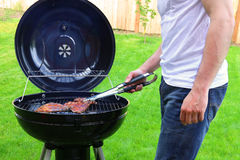Man roasting beef on BBQ grill Royalty Free Stock Image