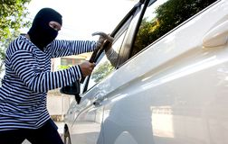 The man robber with a balaclava on his head holding a hammer trying to break into the car stock image