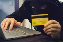 Man in robber mask uses internet, bank account and credit facilities. Phishing attack by male with hidden face. Hacker enters. Stolen financial data stock photo