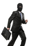 A man in robbery mask carrying a briefcase. Isolated on white background Royalty Free Stock Photography