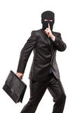 A man in robbery mask stealing a briefcase. Isolated on white background Royalty Free Stock Photography