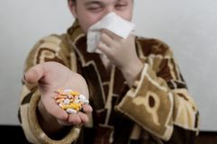 A man in a robe holds a handful of pills and blows his nose in a handkerchief. concept: illness, cold Royalty Free Stock Image