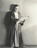 Man in robe reading scroll Stock Photo