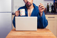 Man in robe working from home and smoking Royalty Free Stock Images