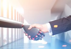 Man and robot handshake, office stock photos